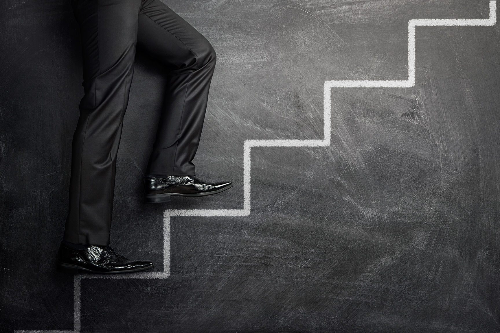 Close up of businessman walking up the career stairs drawn on a black chalkboard with copy space