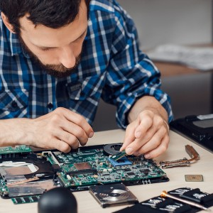 Repairman disassembling laptop motherboard. Engineer fixing broken computer at work. Electronic repair shop, technology renovation, business, occupation concept